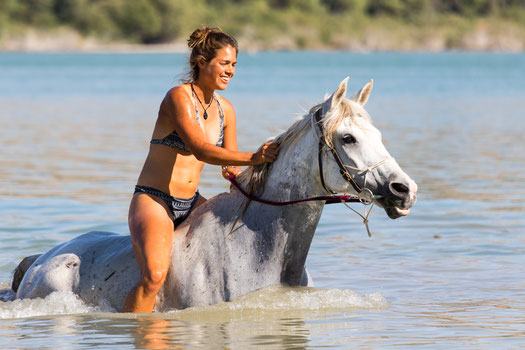 Viviane riding and swimming with the horses.