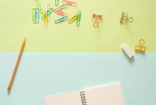 デスク周りのビジネスツール。ノートパソコンのキーボード、付箋、ボールペン、眼鏡、メモ帳、ホッチキス。コーヒーの入ったマグカップ。ミニサイズの多肉植物。