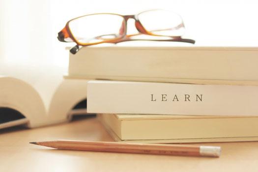 オフィスのデスク。ノートパソコン、眼鏡、スマホ、ページが開かれた手帳、観葉植物。デスクの傍らに通勤カバン。