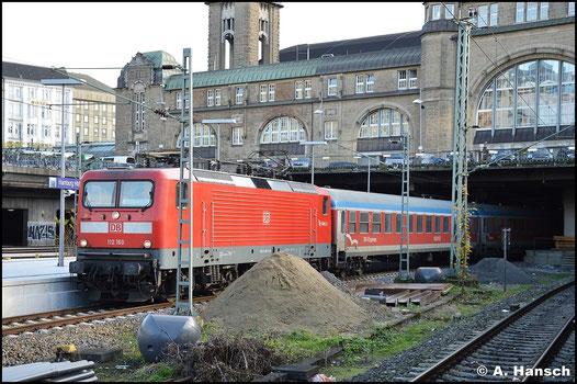 112 160-7 hat am 8. November 2015 die durch den blauen Streifen bestechenden Wagen des Schleswig-Holstein-Express am Haken und wartet in Hamburg Hbf. auf Ausfahrt