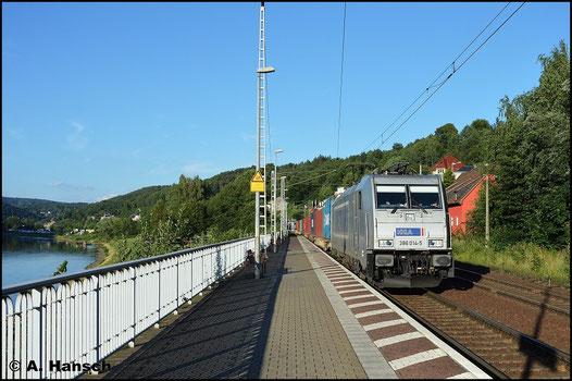 386 014-5 zieht vor der Kulisse der Elbe ihren Containerzug durch den Bf. Königsstein (20. Juli 2015)