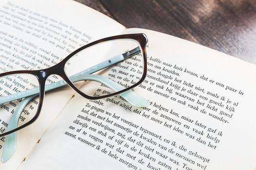 パソコンのキーボードとマウス、電卓、イヤフォン、スマートフォン、コーヒーの入ったカップ&ソーサ。
