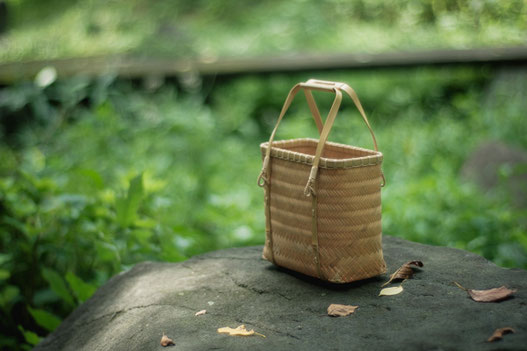 茂る緑と散る葉、竹の手提げ籠