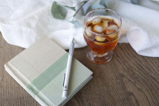 木目調のデスクのうえのノートパソコン、スマホ、雑誌。