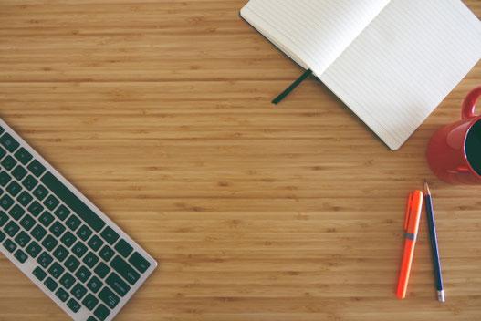 ピンクのバラの花。ナプキンの上に置かれたイチゴチョコのかかったドーナッツ。マグにはいったイチゴミルク。