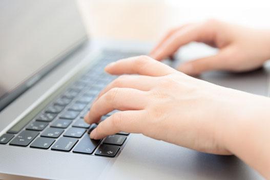 うず高く積まれたファイルの資料に埋もれる社員。手を挙げて助けを求めている。時計は深夜を指している。