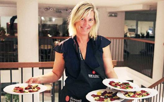 Kvinna serverar fyra tallrikar med mat