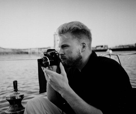 Der Fotograph Tim Schulz aus Hamburg auf einem Segelboot im Hafen von Norderney.