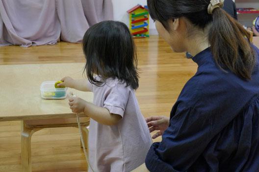 幼児教室のステッラコース(1歳児)のモンテッソーリの活動に取り組んでいる生徒を、母親が後ろで見守っています。
