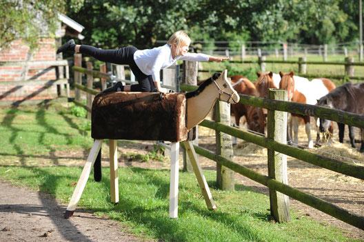 Kleines Mädchen, welches stolz auf einem Voltigierpferd aus Holz trainiert.