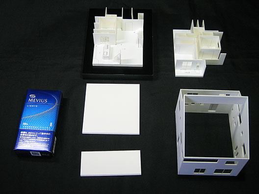 タバコの箱と比較した住宅模型の画像