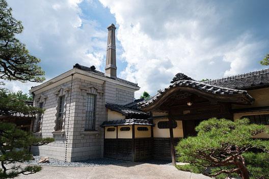 洋風の暖炉と和風の門構えが同居した建物の外観