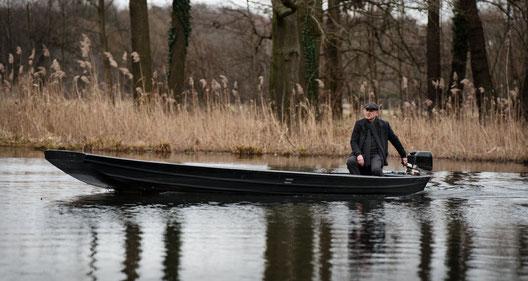 """""""Spreewaldkrimi - Totentanz"""": Thorsten Krüger (Christian Redl) fährt mit einem Motorkahn auf dem Flies im winterlichen, aber schneefreien Spreewald."""