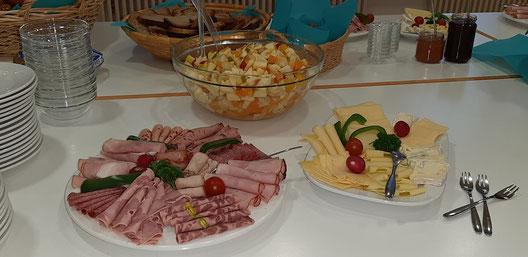 Bild von appetitlich zubereiteten Frühstücksbuffet mit Obstsalat, Wurst und Käse