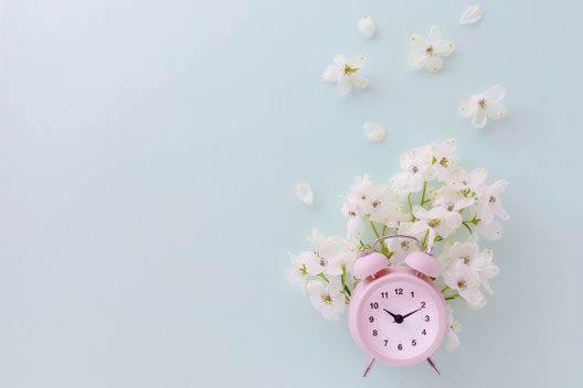 白の目覚まし時計と白の花。