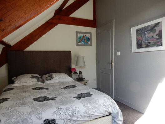 chambre grans lit draps blanc à fleurs grises, moquette grise, tableaux orange et gris au mur blanc