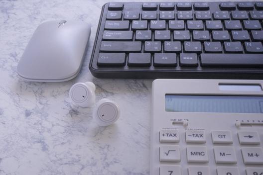 積み重ねられたスケジュール帳、花柄の手帳、リングメモ。ボールペン。スマートフォン。イヤフォン。飲みかけのコーヒーマグ。