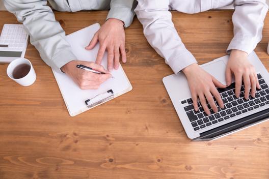 テーブルを囲んでディスカッションするビジネスパーソン。ノートパソコン。テイクアウトコーヒー。