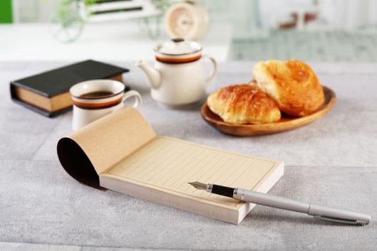 メモ帳と万年筆。コーヒーの入ったマグカップとポット。ハードカバーの書籍。木皿に盛られたクロワッサンとデニッシュ。