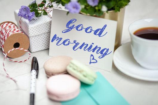 ピンクのテーブルに広げられたノートとペンケース。ガラスの花びんに活けられたピンクと白のガーベラ、カスミソウ。