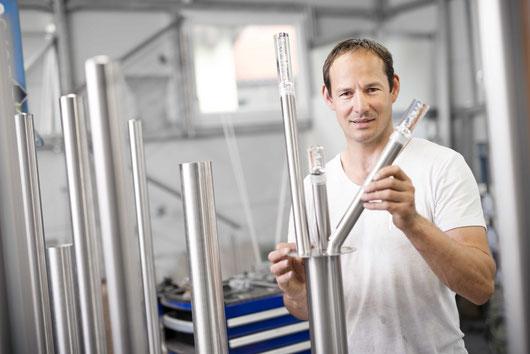 Inhaber Eduard Holzbauer mit seiner Solarleuchte Trio Sticks in seiner Werkstatt