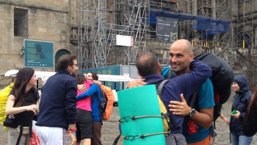 Pilgrims hugging each other at their arrival in Santiago