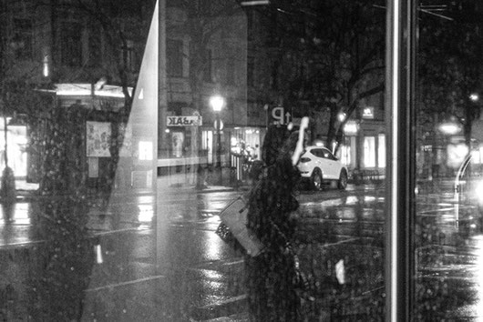 The black and white photo shows the reflection of a night-time street scene