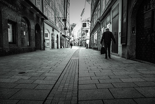 2 men are walking in the otherwise deserted Getreidegasse