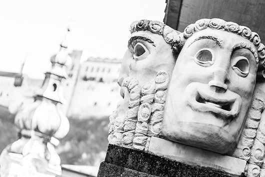 Black and white photo of 2 sculptures at the entrance of the Großes Festspielhaus, Salzburg. In the background the fortress Hohensalzburg