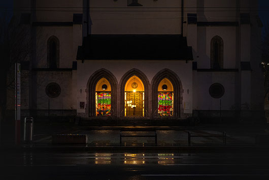 The bright lit entrance of the Andräkirche in Salzburg at night