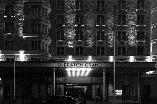 The black and white photo shows the Sheraton Grand, Salzburg at night