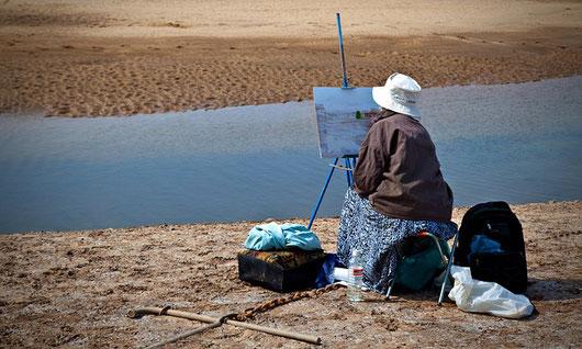 Frau malt am Wasser