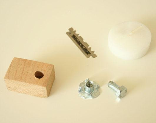 M6-Einschlagmutter, M6-Schraube, einseitig geschliffene Rasierklinge, Holzklötzchen, Teelicht
