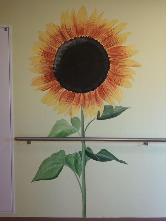 gemalte Sonnenblume im Gang eines Pflegewohnhauses