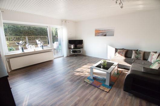 Wohnzimmer mit großer Kuschelcouch und Zugang zu Terrasse und Garten