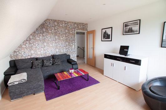 Wohnzimmer mit großer Schlafcouch und Stereoanlag