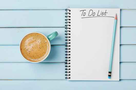 To-Do-Liste und Kaffee auf einem blauen Tisch