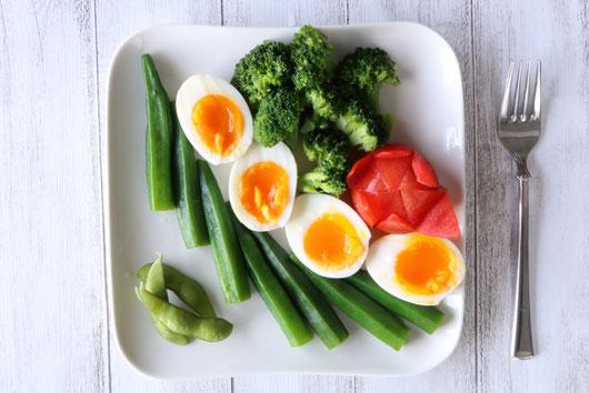 キッチンのカウンターに並べられた野菜たち。たまねぎ、にんじん、ピーマン、トマト、かぼちゃ、ブロッコリー、じゃがいも。計量カップに活けられたハーブ。