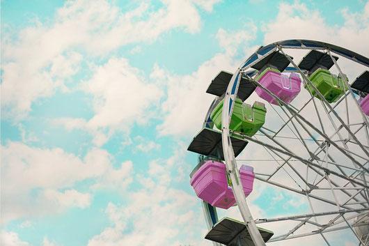 青空に臨む観覧車。グリーンとピンクのボックス。