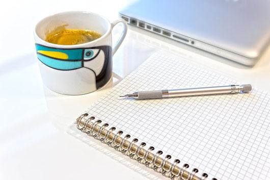 ノートパソコン、方眼紙ノート、シャープペンシル。コーヒーの入ったマグカップ。ペリカンの絵。