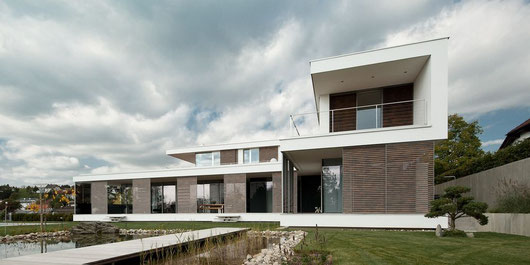 Schiebeläden aus Holz an einer modernen Villa mit einem Pool