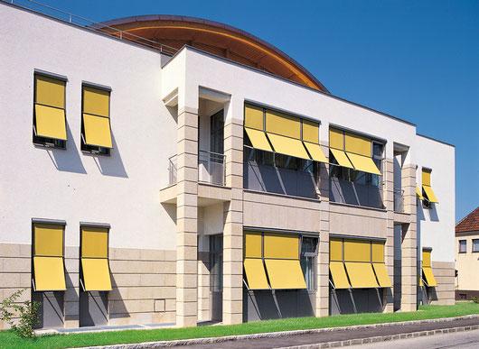 Markisolette von Wo&Wo mit gelben Stoff auf Firmengebäude