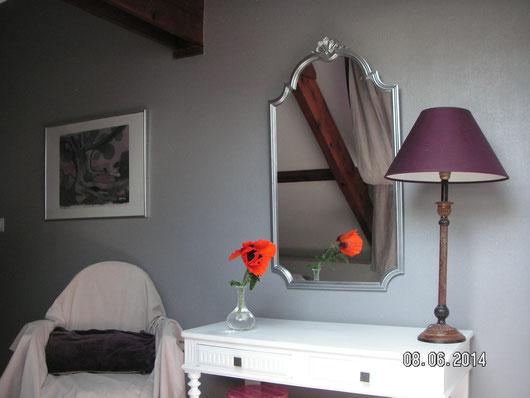 bureau blanc avec fauteuil et fleurs coquelicots, grand miroir argent, lampe sur pied violette