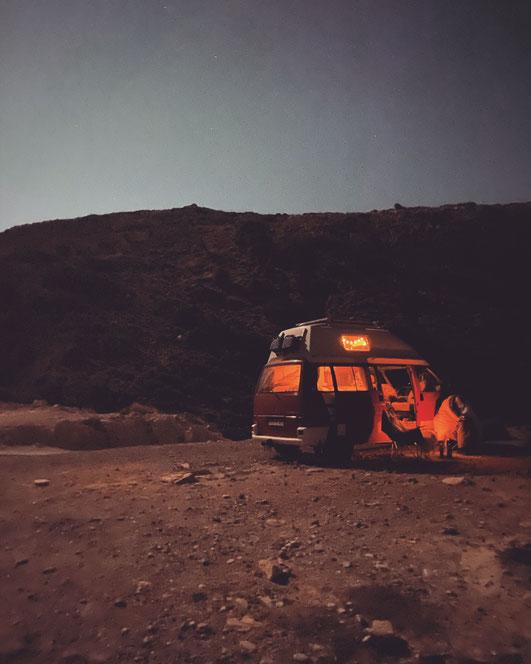 VW Bus abends von innen beleuchtet steht in hügeliger, steiniger Landschaft