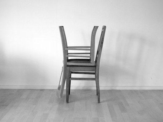 Zwei Stühle stehen zum Wegräumen aufeinandergestapelt