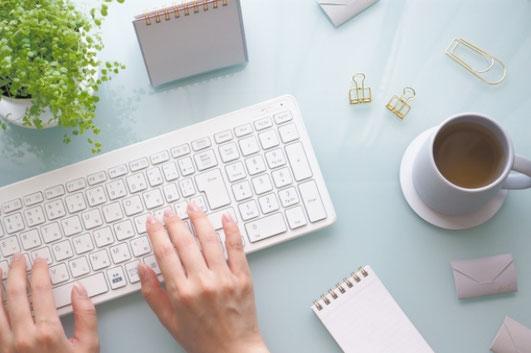 ピンクのノートパソコン。傍らにピンクのバラとダリアのブーケ。
