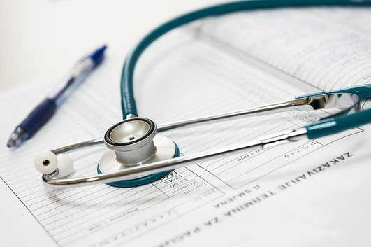診断書と聴診器。ボールペン。