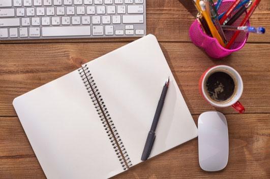 デスクトップパソコンの横に置かれたカップ&ソーサ。観葉植物の鉢植え。卓上カレンダー。