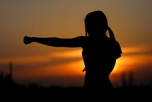 Silhouette einer Frau vor einem Sonnenuntergang, die einen Karateschlag ausführt.