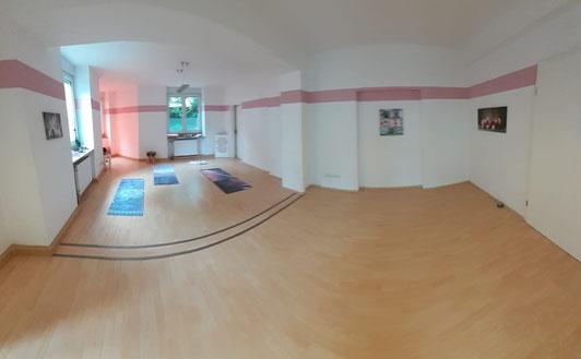Weitwinkel Foto vom Studio helles Laminat mit rosa Bordüren an der Wand und rosa Yogamatten